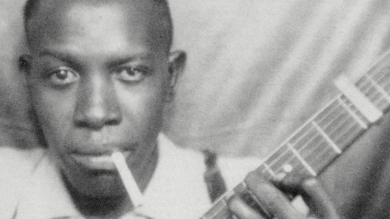Robert Johnson with cigarette and guitar